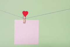 Paper sheets on thread. Serenity paper sheet on thread with heart shaped clothespin on greenery background Stock Photo
