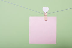 Paper sheets on thread. Serenity paper sheet on thread with heart shaped clothespin on greenery background Royalty Free Stock Image