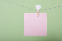 Paper sheets on thread. Serenity paper sheet on thread with heart shaped clothespin on greenery background Royalty Free Stock Photography