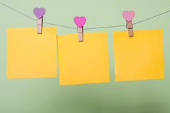 Paper sheets on thread. Yellow paper sheets on thread with heart shaped clothespin on greenery background Stock Images