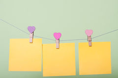 Paper sheets on thread. Yellow paper sheets on thread with heart shaped clothespin on greenery background Stock Photo