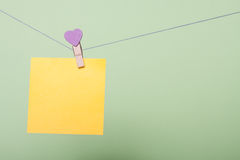 Paper sheets on thread. Yellow paper sheet on thread with heart shaped clothespin on greenery background Royalty Free Stock Photos
