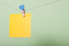 Paper sheets on thread. Yellow paper sheet on thread with heart shaped clothespin on greenery background Stock Images