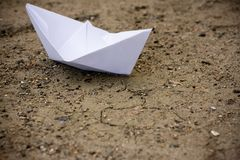 Paper ship. Close-up of paper ship on brown sandy ground Royalty Free Stock Photography
