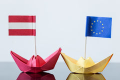 Paper ship with austrian and european flag. Concept shipment or free trade agreement and membership of eu Royalty Free Stock Images