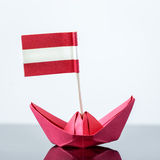 Paper ship with austrian flag. Paper ship with austrian and european flag, concept shipment or free trade agreement and membership of eu Royalty Free Stock Images
