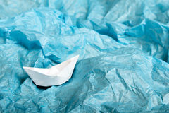 Paper ship in blue tissue paper Stock Photos