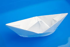 Paper ship in blue water Royalty Free Stock Photo