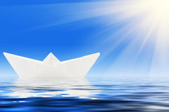 Paper ship and blue water Stock Photos
