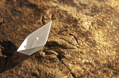 Paper ship on the dried ground Stock Images