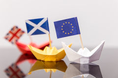 Paper ship with european and scots flag. Broken british flag behind,  concept shipment or free trade agreement and membership of eu, independence referendum Stock Photos