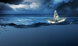 Paper ship. Floating on water on stormy waves Royalty Free Stock Image