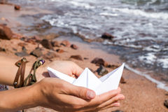Paper ship in hands Stock Image