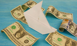 Paper ship sails on waves of money / dollars Stock Photo