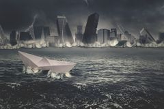 Paper ship in the sinking city Royalty Free Stock Photography