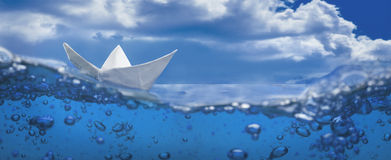 Paper ship splash bubbles sailing blue water sky. Paper ship splash with bubbles sailing in blue water and sky Royalty Free Stock Image