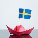 Paper ship with swedish flag. Paper ship with swedish and european flag, concept shipment or free trade agreement and membership of eu Royalty Free Stock Photography