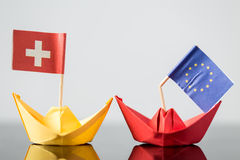 Paper ship with swiss and european flag. Concept shipment or free trade agreement and membership of eu, referendum Royalty Free Stock Photo