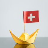 Paper ship with swiss flag. Concept shipment or free trade agreement Royalty Free Stock Images