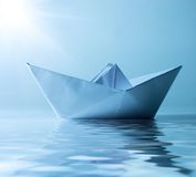 Paper ship in water and sunny blue sky Royalty Free Stock Photos