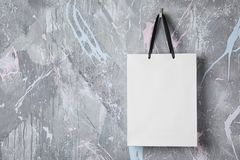 Paper shopping bag with handles hanging. On color wall. Mock up for design royalty free stock image