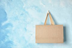 Paper shopping bag with handles hanging on color wall. Mock up for design royalty free stock photos