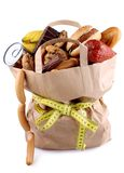 Paper shopping bag with high-calorie foods and measuring tape Stock Photography