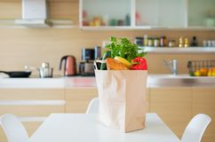Paper shopping bag on kitchen table Royalty Free Stock Images