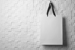 Paper shopping bag with ribbon handles hanging on white wall. Mockup for design royalty free stock images