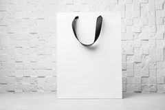 Paper shopping bag with ribbon handles on table near white wall. Mockup for design stock image
