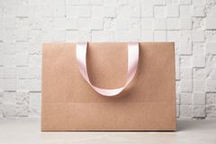 Paper shopping bag with ribbon handles on table near white wall. Mockup for design royalty free stock images