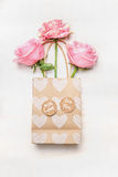 Paper shopping bag with roses and heart on white wooden background, top view.  Valentine Day or Birthday greeting card Stock Photo