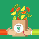 Paper shopping bag with sliced fruits in human hands. Vector ico Stock Photos