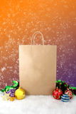 Paper shopping bags christmas decoration with balls and stars on snow bokeh vintage background Stock Photos