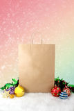Paper shopping bags christmas decoration with balls and stars on snow bokeh vintage background. Red and green Stock Photo