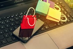 Paper shopping bags with mobile phone on notebook keyboard. Conc Royalty Free Stock Image