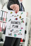 Business plan concept shown by a businessman. Paper showing business plan concept held by a businessman stock photography