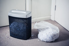 Paper shredder and bag of shredded documents. A paper shredder and a bag of shredded documents by the door Royalty Free Stock Image