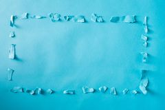 Paper shreds in a frame or border shape. On a blue background Royalty Free Stock Photography