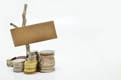 Paper sign board with stack of coins Stock Image