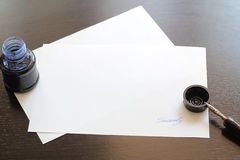 Paper with sign ink and fountain pen on wood desk Royalty Free Stock Photo