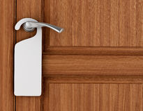 Paper signboard hanging on a handle of door. Royalty Free Stock Image