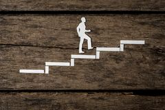 Paper silhouette cutout of a man climbing the stairs. Over rustic wood Stock Photography
