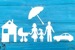Paper silhouette of family with baby carriage under umbrella. Car and house on blue wooden background. Life insurance concept Stock Images