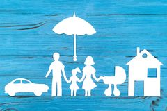 Paper silhouette of family with baby carriage under umbrella. Car and house on blue wooden background. Life insurance concept Royalty Free Stock Image