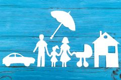 Paper silhouette of family with baby carriage under umbrella. Car and house on blue wooden background. Life insurance concept Stock Photos