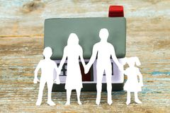 Paper silhouette of family and house  on wooden desk . insurance Royalty Free Stock Photo