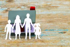 Paper silhouette of family and house  on wooden desk . insurance Royalty Free Stock Photos