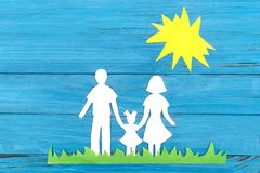 Paper silhouette of a family standing on the green grass under the sun. On blue wooden background. Concept of family love Royalty Free Stock Image