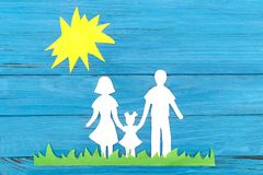 Paper silhouette of a family standing on the green grass under the sun. On blue wooden background. Concept of family love Royalty Free Stock Photo